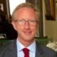 Lars Kinnunen porträttbild. Lars är iklädd kostym och glasögon, han har ljust kort hår