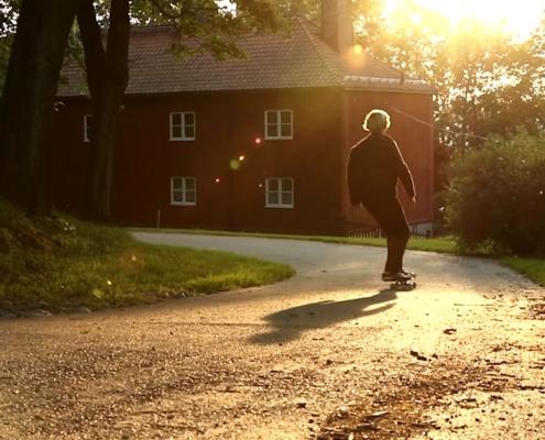 Vilmer Bäckman åker skateboard ner för en backe i motljus