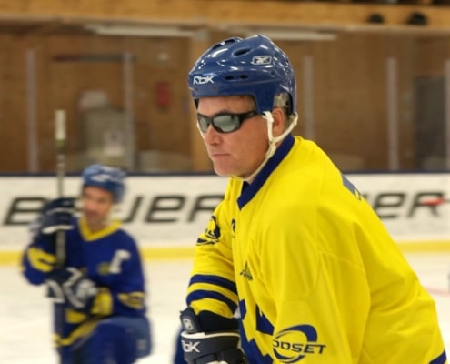 Blind Ice Hockey, man i gulblå hockeytröja, hjälm och mörka glasögon