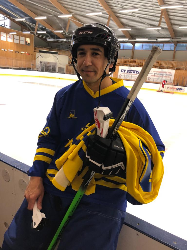 Blind Icehockey, en person iförd hockeyutrustning står med en hockeyrink i bakgrunden