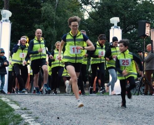 En grupp springer med gula västar på en grusväg med publik på sidorna. Det syns gröna träd i bakgrunden.