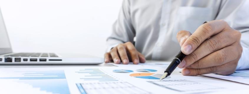 Ekonomirapport ligger utskriven på skrivbord bredvid dator. En person antecknar på papperen.